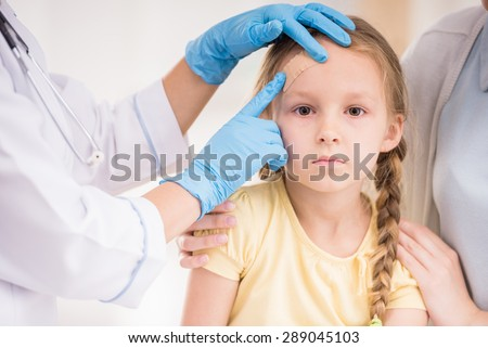 Pediatrician doctor getting plaster to child's wound. Close-up.
