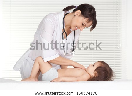 Pediatrician doctor with little girl on white background - stock photo