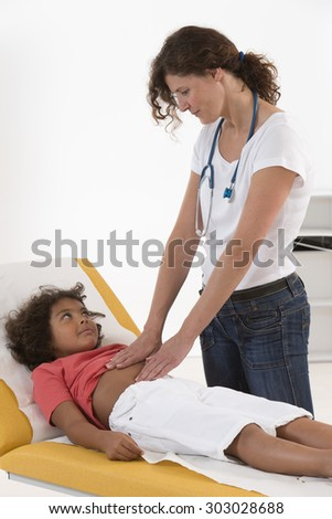 pediatrician doing abdominal examination - stock photo