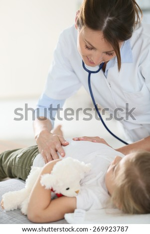 Pediatrician examining child's stomach