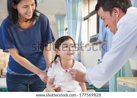 pediatrician examining little girl , her mother beside her - stock photo