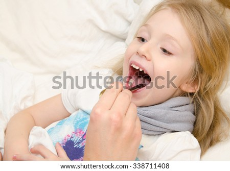Pediatrician examining little girl's throat - stock photo