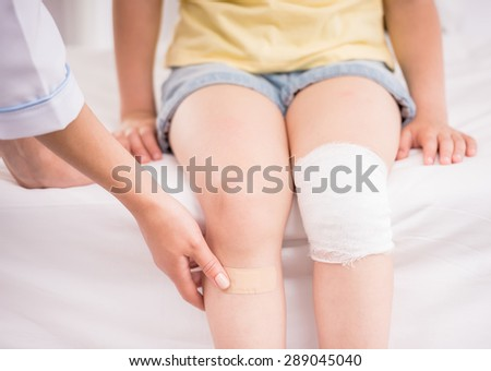 Pediatrician female doctor bandaging child's leg. Close-up. - stock photo