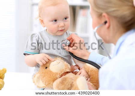 Pediatrician is taking care of baby in hospital. Little girl is being examine by doctor with stethoscope. Health care, insurance and help concept.