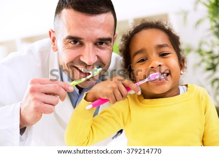 Pediatrician learn cute african girl brushing tooth, healthy concept - stock photo