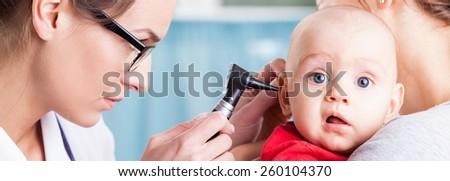 Pediatrician using otoscope to examine baby's ear - stock photo