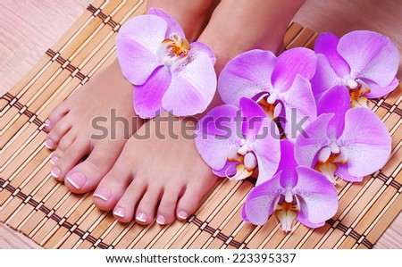 Pedicure. Female feet with pink orchid flowers on bamboo mat. Foot care. Spa
