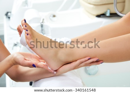 Pedicure moisturizing cram after dead skin remover foot rasp woman in nail salon - stock photo