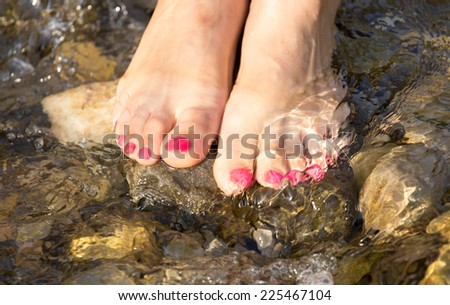 pedicure on foot in the water on the rocks - stock photo