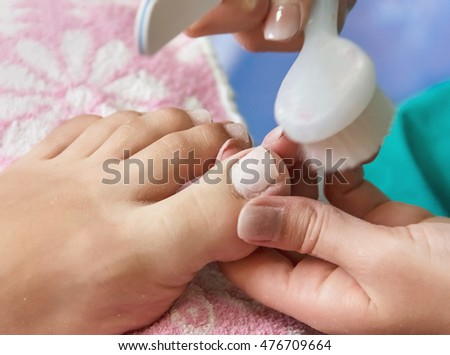 pedicure, pedicure process professional in the beauty salon, clean cuticles and nail on his feet, Treatment and Foot Care