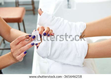 Pedicure treatment to woman feet in nails salon on sofa chair - stock photo