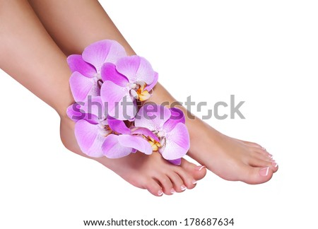 Pedicure with pink orchid flowers isolated on white. Beautiful female feet with french manicure. Foot care. Spa - stock photo