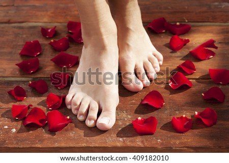 Pedicure, woman legs surround with rose petals