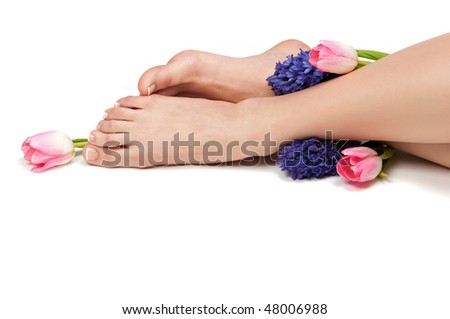 Pedicured feet and aromatic flowers in a spa - stock photo