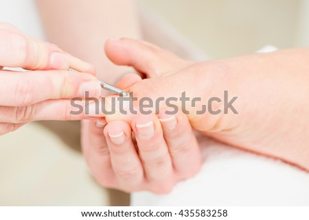 Pedicuring in beauty salon. Close-up, high key, selective focus - stock photo