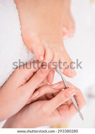 Pedicurist master makes pedicure on woman's leg. Spa treatment. - stock photo