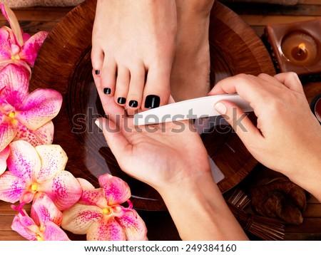 Pedicurist master makes pedicure on woman's legs - Spa treatment concept - stock photo
