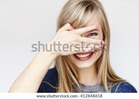 Peeking young blond woman smiling at camera - stock photo