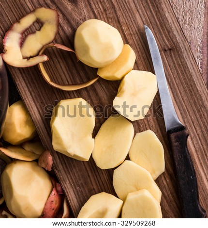 peeled and cut potato on board with knife