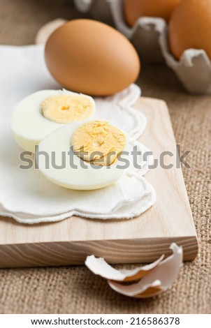 peeled and sliced hard-boiled egg on white cloth with several whole eggs in the background - stock photo