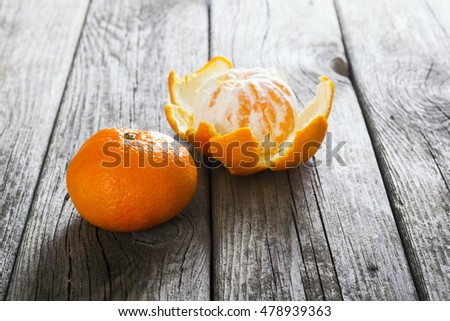 peeled and whole tangerines on old wood table