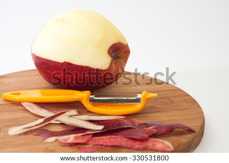 Peeled apples on a wooden board with a tool for peeling.