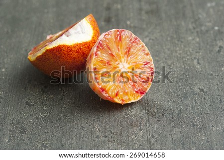 peeled blood orange on dark wood table - stock photo