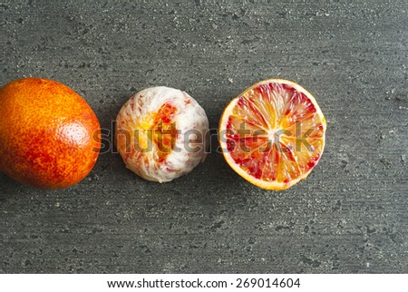 peeled blood oranges on dark wood table - stock photo