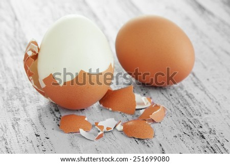 Peeled boiled egg on wooden background - stock photo