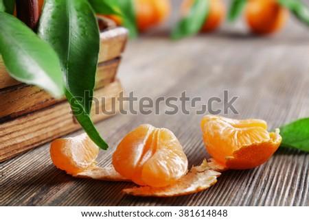 Peeled fresh tangerine on wooden table, closeup - stock photo