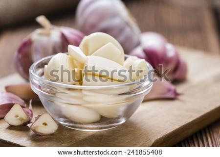 Peeled Garlic (close-up shot) on vintage wooden background - stock photo