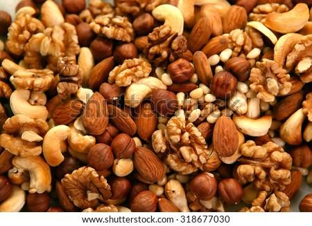 Peeled nuts in bulk as background: walnut, almonds, cashews - stock photo