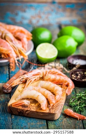 peeled raw prawns on a wooden cutting board with salt, pepper, lime on a rustic table - stock photo