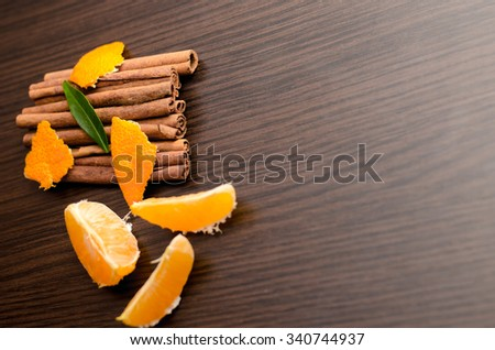 Peeled tangerine and cinnamon sticks, segments isolated on black background,horizontal photo