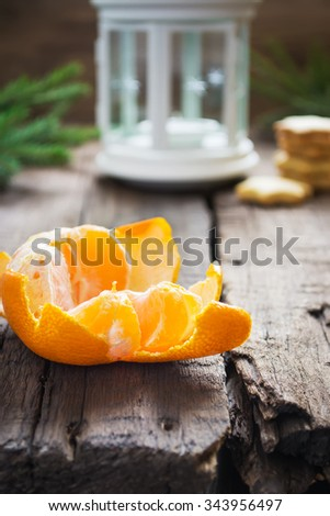 Peeled tangerine, ginger biscuits and white lights on a Christmas background