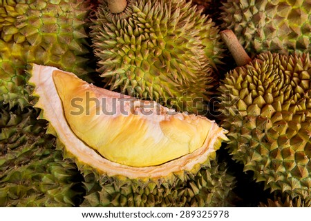 Peeled yellow Mon Thong durian on heap of durian fruits  - stock photo