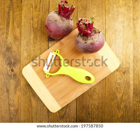Peeler and beet on wooden table