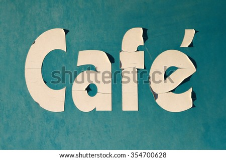 """Peeling """"Cafe"""" sign in sunlight with shadows  - stock photo"""