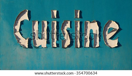 """Peeling """"Cuisine"""" sign in sunlight with shadows  - stock photo"""