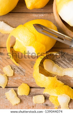Peeling lemons on wooden table. Shallow depth of field. - stock photo