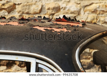 Peeling paint on old car wreck  roof - stock photo