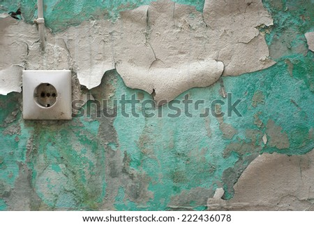 Peeling paint on old wall with an electrical outlet - stock photo
