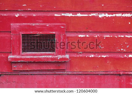 Peeling red paint on a weathered wooden wall with a screened air vent. Close up detail. - stock photo