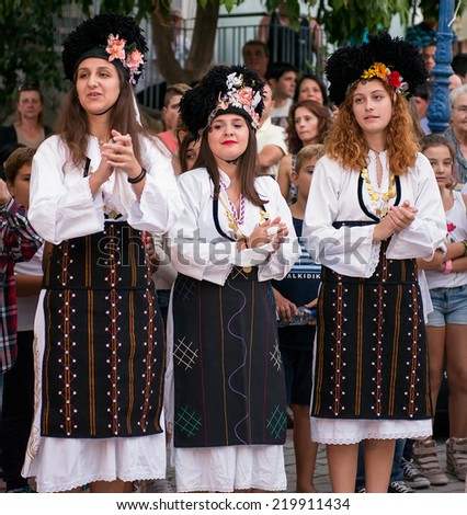 PEFKOHORI , GREECE - SEPTEMBER 19 2014 : Folk Dancers from several countries  taking part in the Annual Folk Dance festival in the village square of Pefkohori ,Greece - stock photo