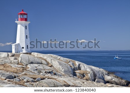 Peggy's Cove lighthouse, Nova Scotia, Canada.  Lobster boat gathering traps in the background. - stock photo