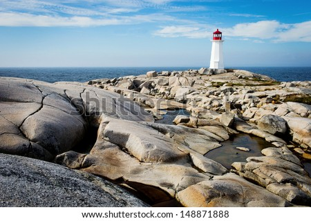 Peggy's Point Lighthouse in Nova Scotia Canada with blue sky and rocks in foreground - stock photo