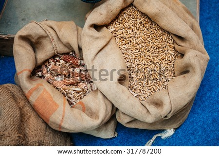Pellets compressed organic matter, or, biomass made from energy crops in their organic bags next to eachother - stock photo