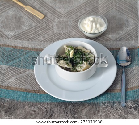 Pelmeni in a bowl with melted butter and chopped dill on the linen table cloth - stock photo