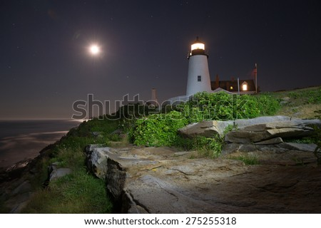 Pemaquid Point Lighthouse at night lit by flashlight and moonlight, Maine, USA. - stock photo