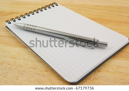 Pen and blank note pad on wooden background